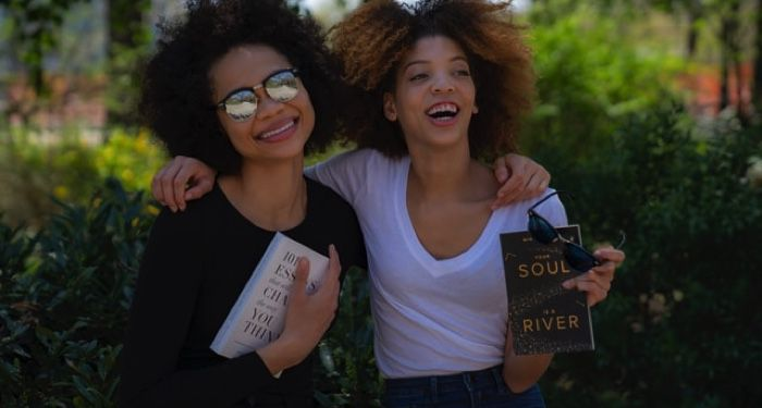 two women smiling, hugging, and holding books