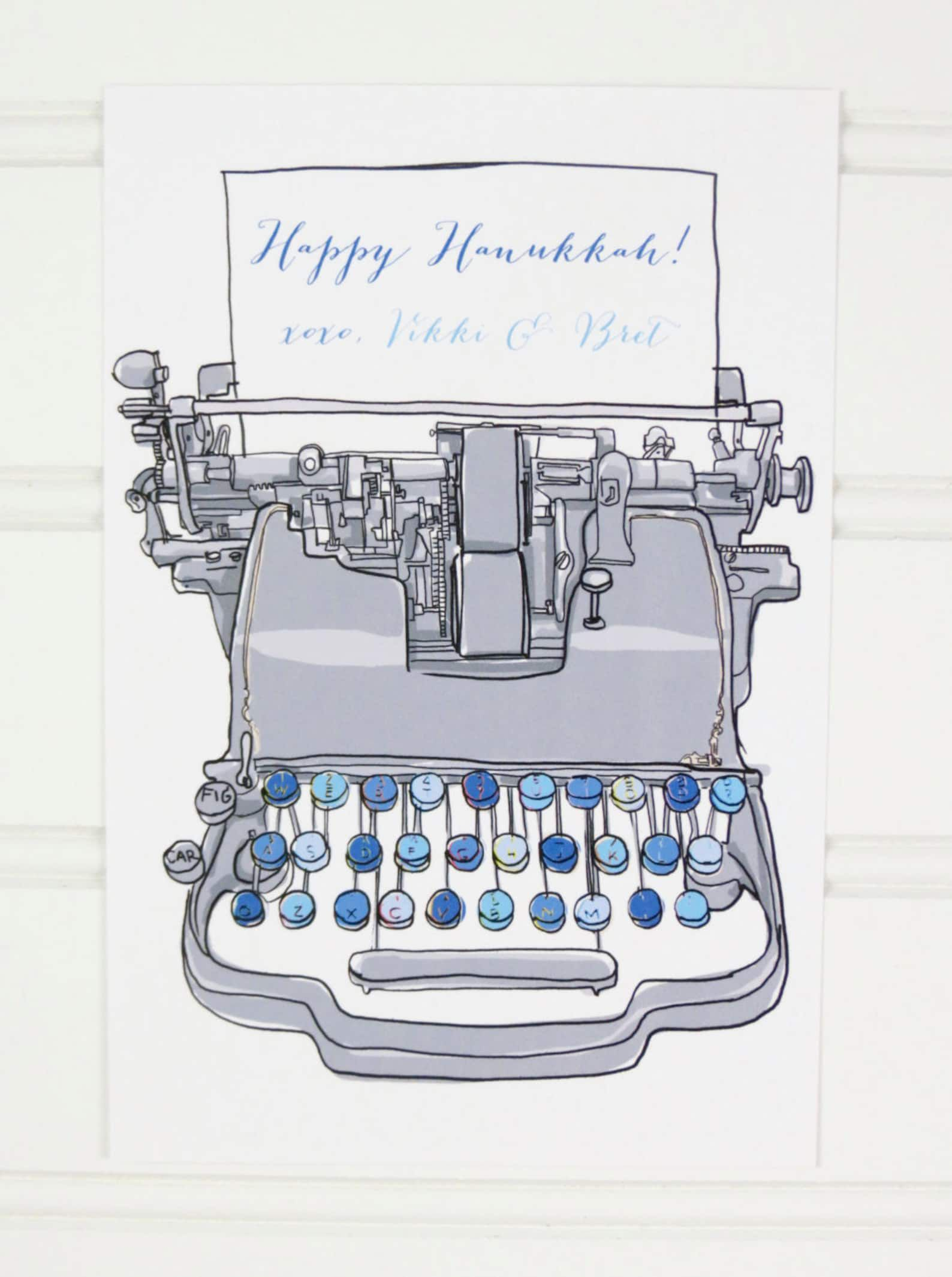 """A vintage blue typewriter typing out """"Happy Hanukkah"""" with space for a personalized message on a white postcard"""