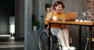 a person in a wheel chair waving in greeting at her laptop screen