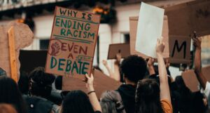 why is ending racism even a debate protest sign