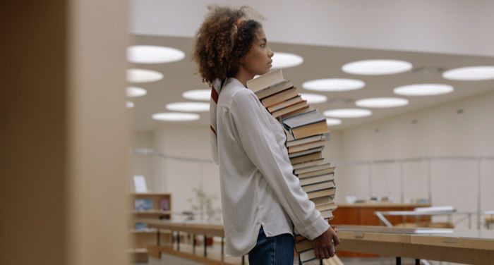 a woman carrying a large stack of books