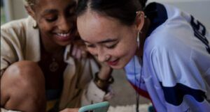 image of women looking at phone and smiling