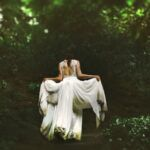 image of a woman in a white dress walking through the woods