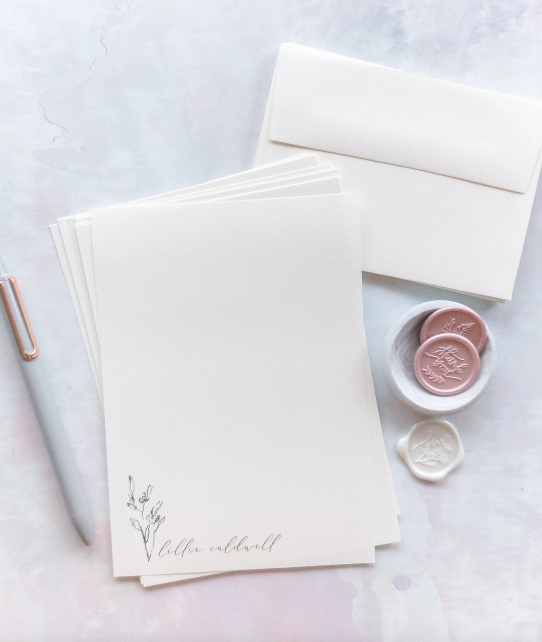 Cream colored stationary with white pen and pink and white wax buttons