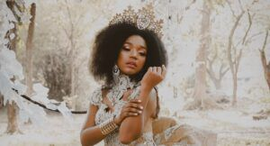 a photo of a Black woman wearing a crown in a wintry forest