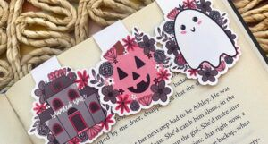 An open book with three magnetic bookmarks: a grey haunted house with pink florals, a pink jack-o-lantern, and a white ghost with pink florals.