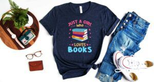 """A flatlay centered around a navy t-shirt that reads """"Just a girl who loves books"""" with colorful book spines and hearts, surrounded by jeans, sneakers, glasses, a watch and camera and a wallet."""