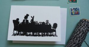 A greeting card with a black silhouette of the characters from Alice in Wonderland at a tea party,