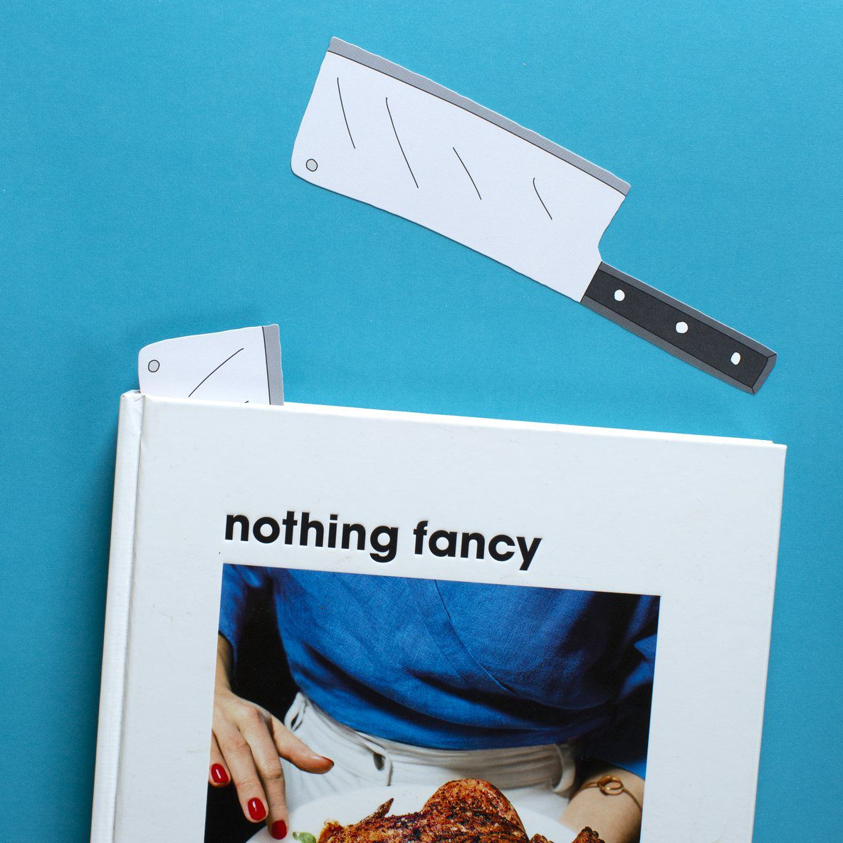 A bookmark in the shape of a cleaver against a blue background, next to a cookbook