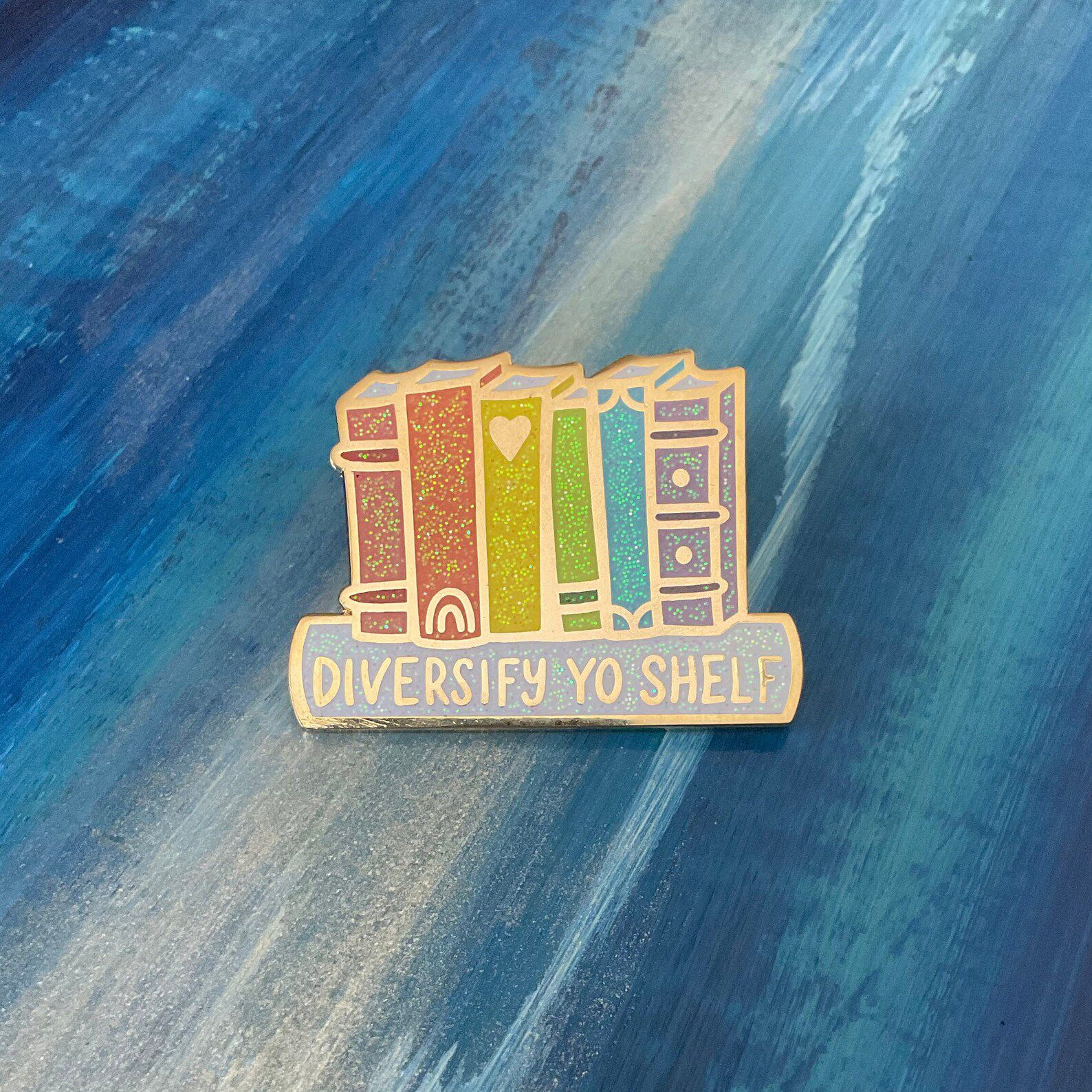 """An enamel pin of rainbow book spines with the words """"diversify yo shelf."""""""