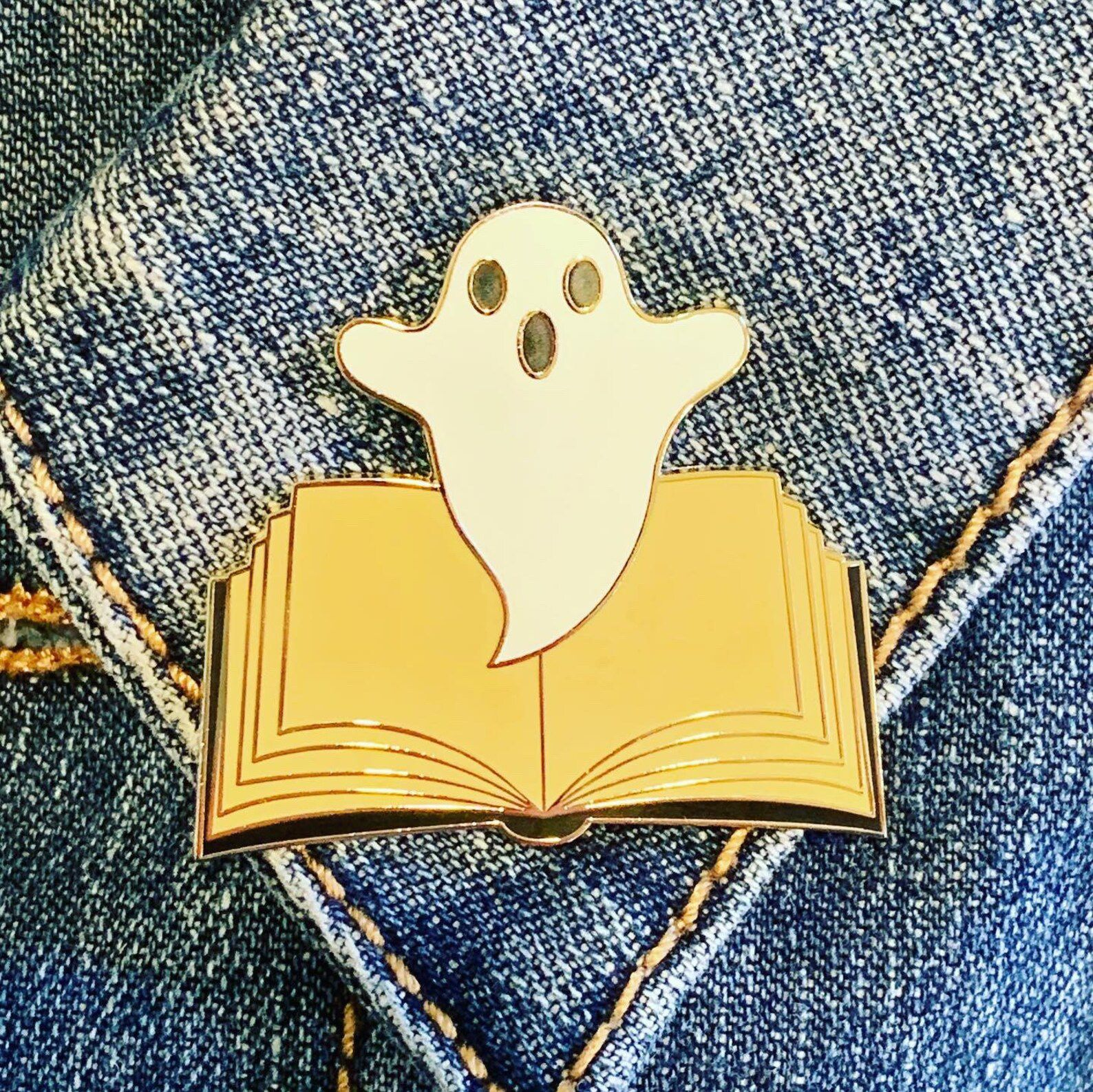 A pin of a small white ghost floating out of an open book.