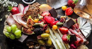 a grazing board full of fresh and dried fruits, assorted meats and cheeses, and other snacks