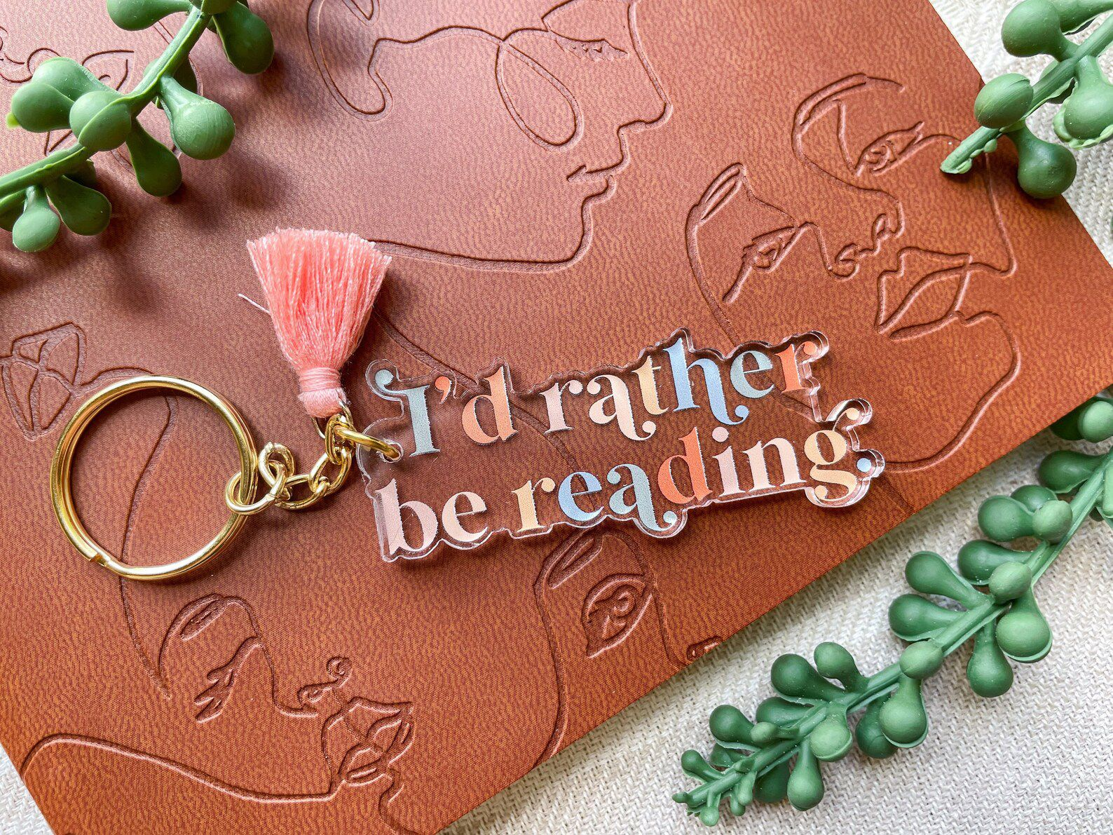 """A clear acrylic keychain with pink and blue lettering that reads """"I'd rather be reading"""" with a pink tassels on a gold keyring."""
