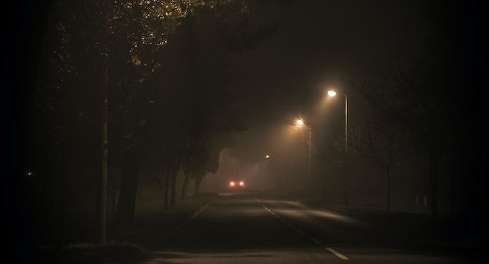 Image of a car driving down a dark road