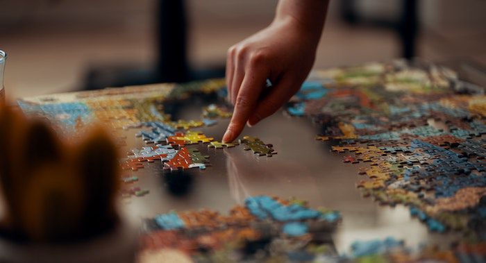 Image of a hand putting together a puzzle