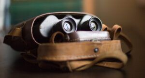 Image of binoculars in a bag with a notebook
