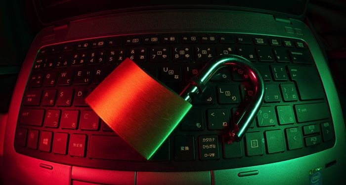 a padlock resting on a laptop keyboard, image is bathed in red and green light