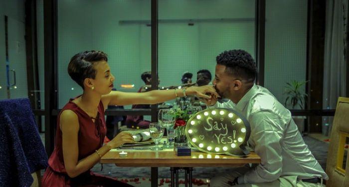 man and woman sitting at restaurant; man kissing woman's hand