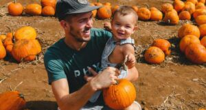 image of man holding baby in pumpkin patch