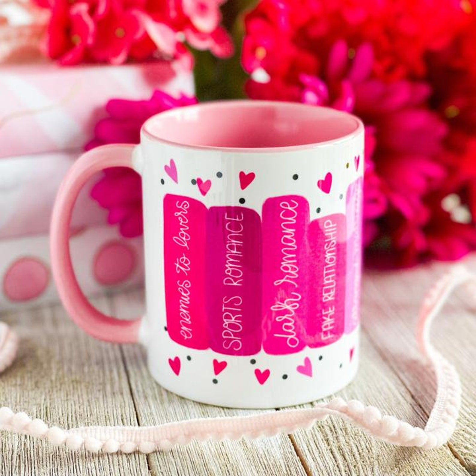 A white and pink mug featuring book spines with various romance tropes.