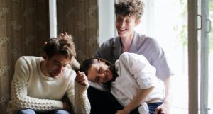 two men and a woman cuddled up and laughing together