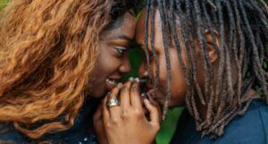 two Black women staring into each others eyes and holding hands