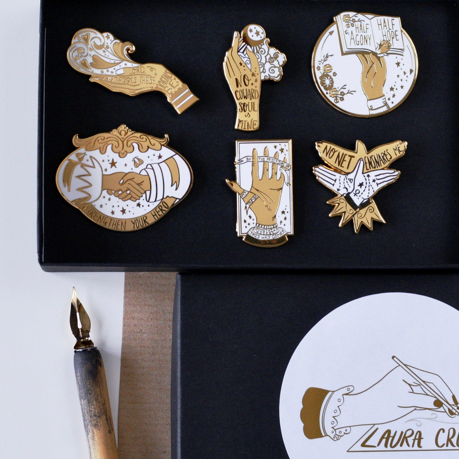 A set of six white and gold enamel pins featuring various illustrations of hands and florals, along with quotes from classic Victorian literature