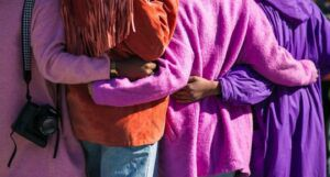 four women in purple holding each other with backs to the camera
